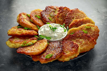 Potato pancakes, draniki, hash browns or fritters served with fresh cream and spring onion