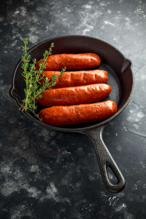 Freshly made raw breed butchers sausages in rustic skillet.