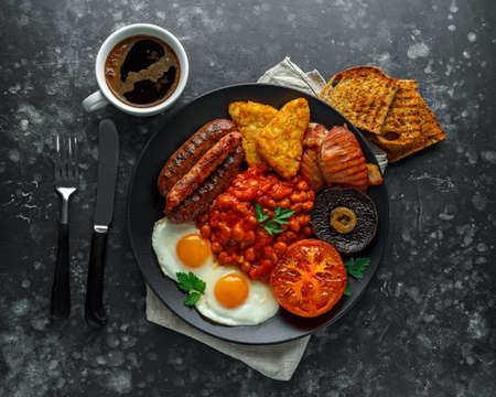 Full English breakfast with bacon, sausage, fried egg, baked beans, hash browns and mushrooms in black plate. cup coffee.