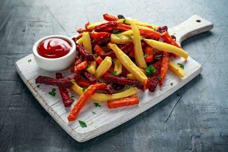 Homemade Baked Mixed Vegetable Fries beetroot, carrot and parsnip with ketchup. on white wooden board.