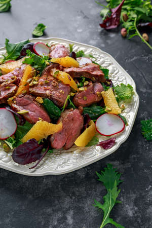 Duck breast fillets steak salad with orange halves, radishes and crushed pistachios Imagens