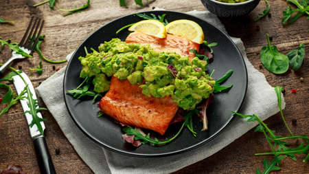 Oven cooked salmon steak, fillet with avocado salsa and green on black plate. wooden table. healthy food 版權商用圖片 - 95918992