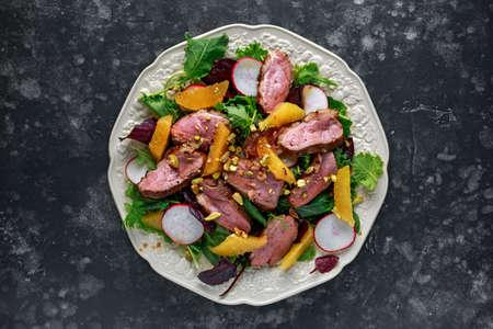 Duck breast fillets steak salad with orange halves, radishes and crushed pistachios Reklamní fotografie