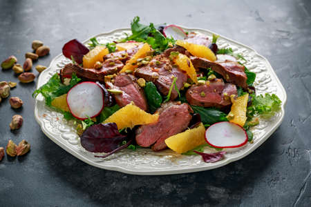 Duck fillets steak salad with orange halves, radishes and crushed pistachios