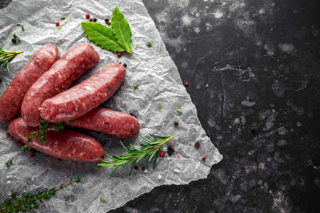 Freshly made raw breed butchers sausages in skins with herbs on crumpled paper.