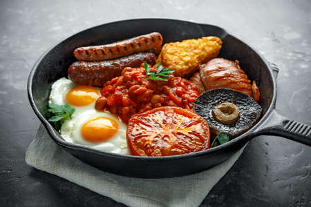 Full English breakfast with bacon, sausage, fried egg, baked beans, hash browns and mushrooms in rustic skillet, pan. 版權商用圖片