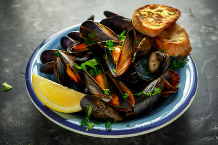 Mussels in garlic butter sauce served with parsley, toast and lemon Imagens