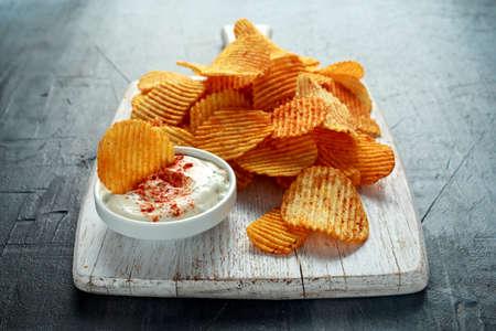 ポテトチップス、ホワイトボードに赤パプリカとホワイトディップソースのスナッククリスプ。 写真素材
