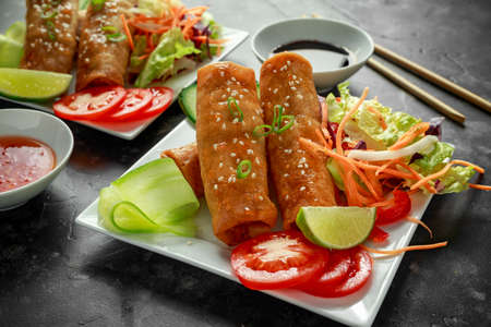 Chinese vegetable spring rolls garnished with fresh salad, lime wedges, sweet chilli sauce and soy sauce Archivio Fotografico