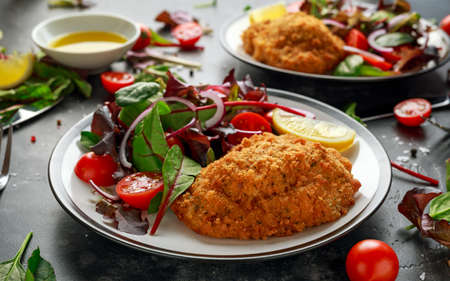 Breaded Chicken Kiev breast stuffed with butter, garlic and herbs served with vegetables in a plate.