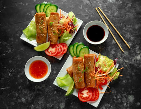 Chinese vegetable spring rolls garnished with fresh salad, lime wedges, sweet chilli sauce and soy sauce 写真素材