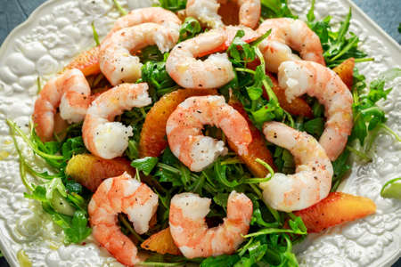 Asian style shrimp salad with wild rocket and blood orange served with lemon wedges and balsamic vinegar drizzle