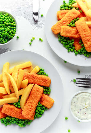 British Traditional Fish finger and chips with peas and tartar sauce in a white plate. Фото со стока