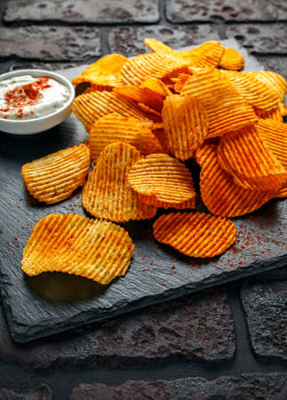 Potato chips, snack crisps with red paprika and white dip sauce