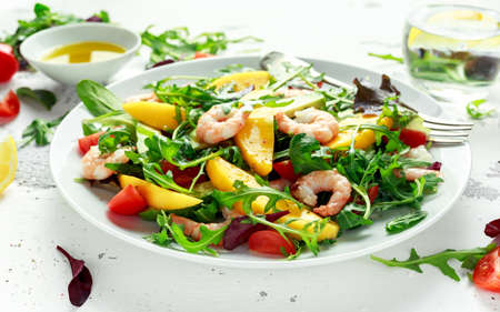 Fresh Avocado, Shrimps, Mango salad with lettuce green mix, cherry tomatoes, herbs and olive oil, lemon dressing. healthy food.