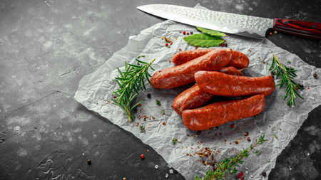 Freshly made raw breed butchers sausages in skins with herbs on crumpled paper. Archivio Fotografico - 99124031