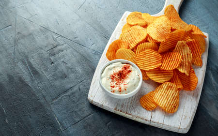 Potato chips, snack crisps with red paprika and white dip sauce on white board.