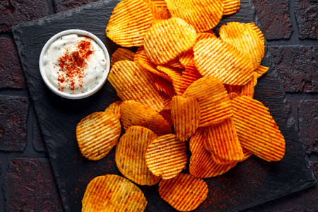Potato chips, snack crisps with red paprika and white dip sauce Stock Photo