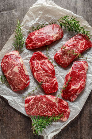 Raw organic Marbled beef steaks with rosemary and thyme on cooking paper 스톡 콘텐츠
