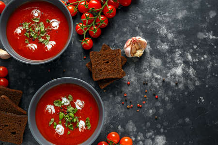 Tomato and fresh basil soup with garlic, cracked papper corns, served with cream and sourdough bread Stock fotó