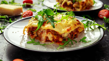 Homemade lasagna with minced beef bolognese and bechamel sauce topped wild arugula, parmesan cheese