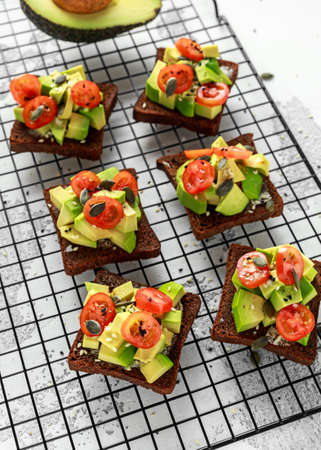 Healthy Avocado and cherry tomato rye sourdough toasts with pumpkin, sesame and nigella seeds, drizzled with olive oil and sea salt flakes served on wooden board Stock Photo