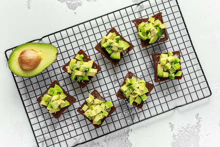 Healthy Avocado rye sourdough toasts with sesame seeds, drizzled with olive oil and sea salt flakes.