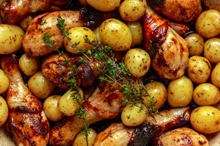 Oven baked Chicken drumsticks and new baby potatoes with thyme in pan, ready to serve