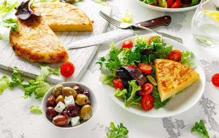 Spanish tortilla, omelette with potato, onion, vegetables, tomatoes, olives and herbs in a white plate. breakfast, healthy food.