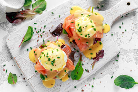 Eggs Benedict on english muffin with smoked salmon, lettuce salad mix and hollandaise sauce on white board.