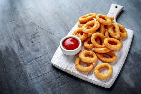 Fried Onion Rings with Ketchup on white cutting board.