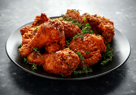 Cosce di pollo croccanti fritte, coscia in un piatto nero alle erbe.