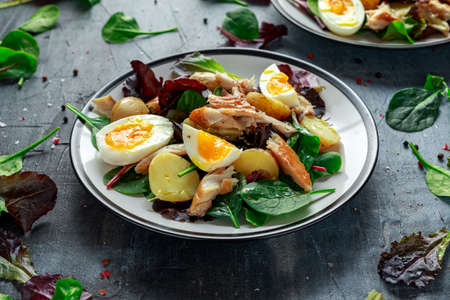 Warm Smoked Mackerel Salad with new potato, eggs, green lettuce mix in a plate.
