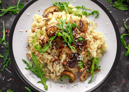 Italian Mushroom risotto with parmesan cheese and wild rocket on top. Archivio Fotografico - 100868813