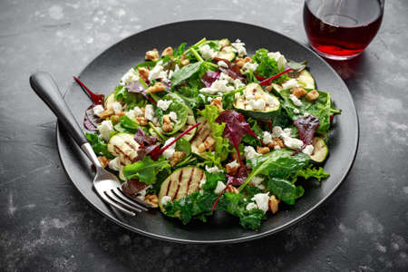 Grilled Zucchini salad with feta cheese, walnut nuts and glass of red wine in a black plate. Zdjęcie Seryjne