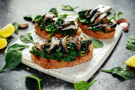 Mushrooms and garlic sauteed spinach toasts With lemon wedges. healthy food.