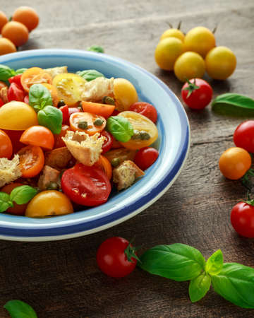 Homemade Panzanella, Tomato traditional Italian salad with red, yellow, orange cherry tomatoes, capers, basil and ciabatta croutons. summer healthy food. Banque d'images - 101230203