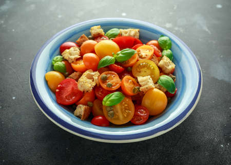 Homemade Panzanella, Tomato traditional Italian salad with red, yellow, orange cherry tomatoes, capers, basil and ciabatta croutons. summer healthy food. Stock Photo