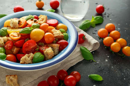 Homemade Panzanella, Tomato traditional Italian salad with red, yellow, orange cherry tomatoes, capers, basil and ciabatta croutons. summer healthy food. Banque d'images - 101230211