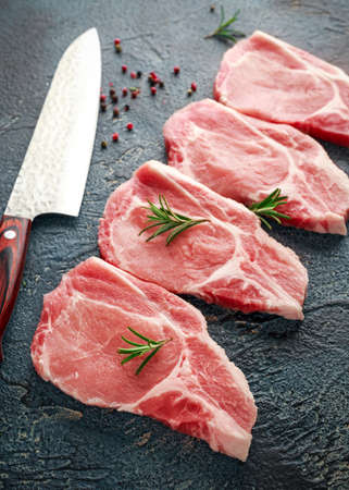 Raw Pork Loin chops with herbs, rosemary, thyme, pepper and knife