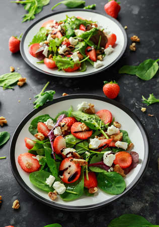 Summer Fruit Strawberry, spinach Salad with walnut, feta cheese balsamic vinegar, kale. in a plate. concepts health food