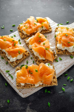 Homemade Crispbread toast with Smoked Salmon and soft chees, chives on white board Stock Photo