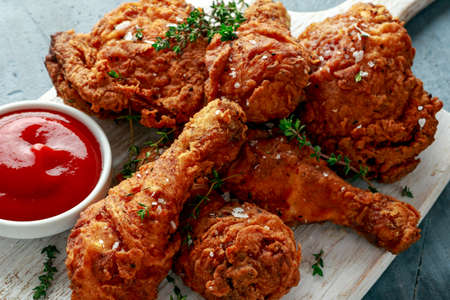 Fried crispy chicken legs, Thigh on white cutting board with ketchup and herbs 版權商用圖片