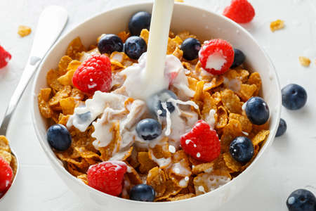 Healthy Morning Breakfast honey Corn flakes with fresh fruits of Raspberry, blueberries and pouring milk in bowl. Stok Fotoğraf