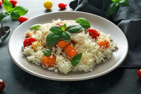 Gestoomde kabeljauw met rijst en cherry mix tomaten en basilicum kruiden in een bord