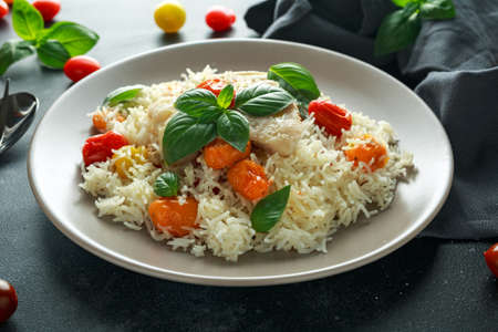 Steamed cod fish with rice and cherry mix tomatoes and basil herbs in a plate 版權商用圖片 - 103953232