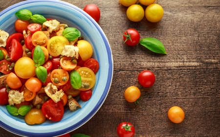 Panzanella Tomato salad with red, yellow, orange cherry tomatoes, capers, basil and ciabatta croutons. summer healthy food. Banque d'images - 103953428