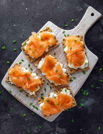 Homemade Crispbread toast with Smoked Salmon and soft chees, chives on white board Foto de archivo