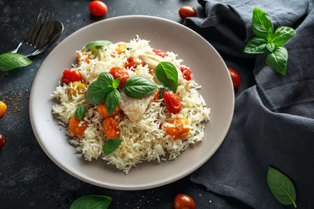 Steamed cod fish with rice and cherry mix tomatoes and basil herbs in a plate
