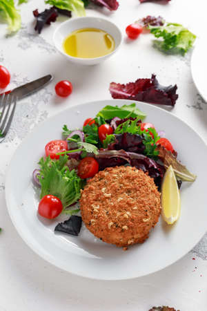 Home made Fish Cake salmon, spinach and potato. served on plate with vegetables Stock Photo